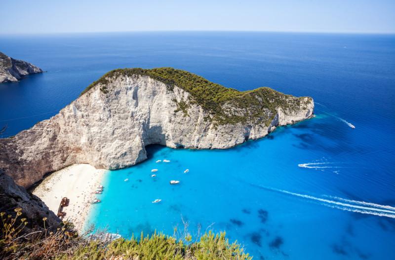 la famosa spiaggia di navagio in Grecia con molte barche in giro per la Grecia